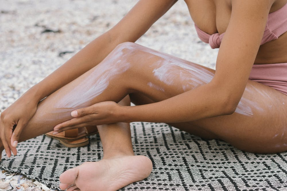 girl putting on suncream on beach