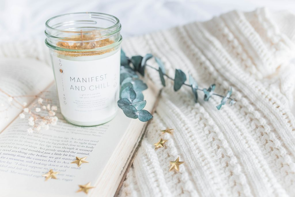 manifest candle with a book - self-love new years resolutions
