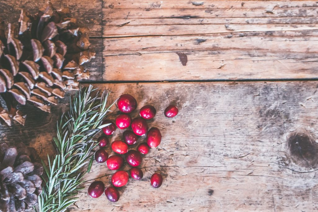 pine cone and berries on a wooden table